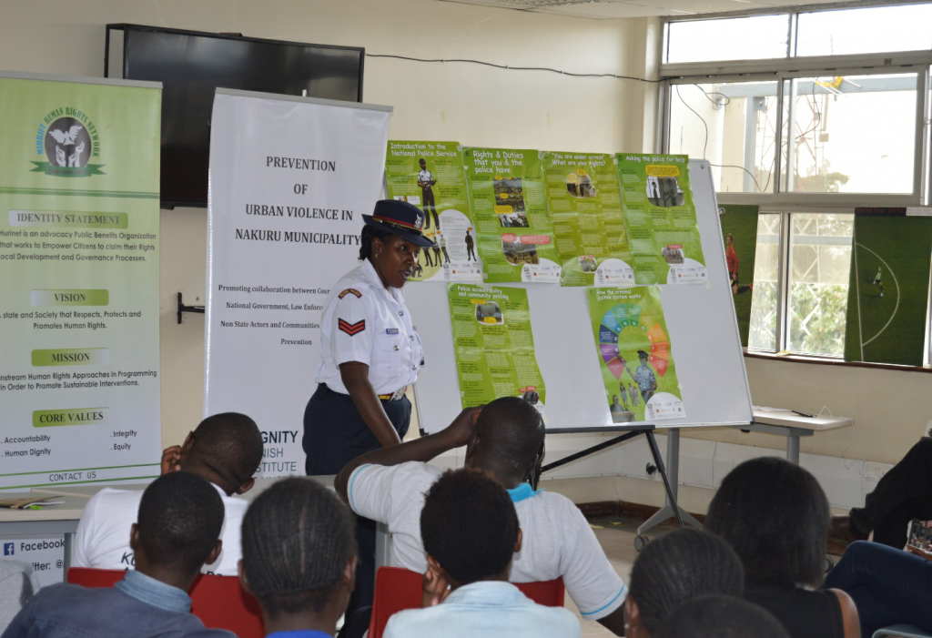 Gender officer from Kaptembwo police station leading discussions on 101 Q&A booklet on police at KNLS Nakuru Library